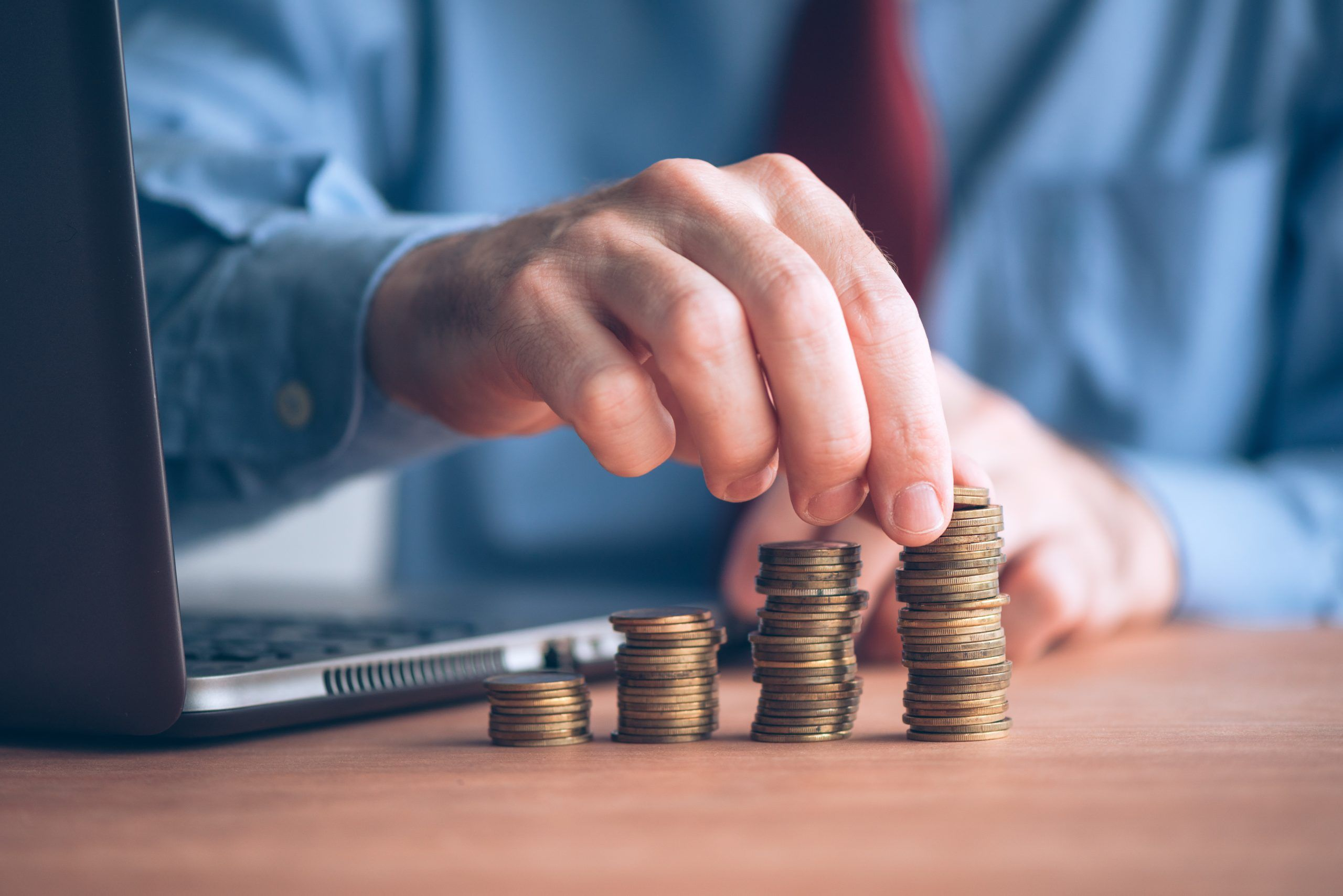 Building savings and increase emergency funds, businessman with stacked money coins on office desk